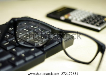 closeup of glasses , keyboard and calculator on table with a very shallow depth of field with copy space for text