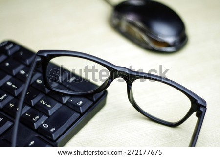 closeup of glasses , keyboard and mouse on table with a very shallow depth of field with copy space for text
