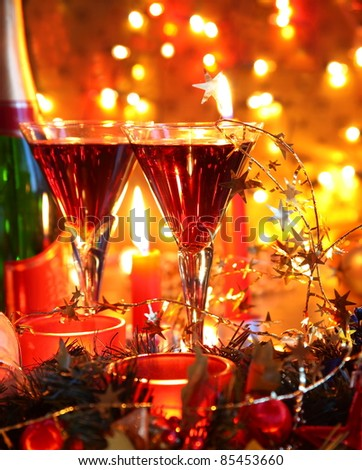Closeup of glasses of red wine and candle lights on golden background with twinkle lights. - stock photo