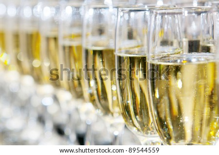 Closeup of glasses of white wine in a row on a table - stock photo