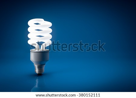 Closeup of glowing energy saving bulb over blue background - stock photo