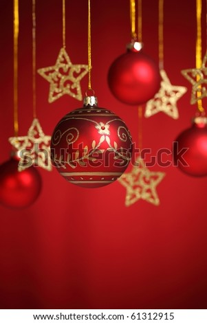 Closeup of gold star and christms bauble on red  background. - stock photo