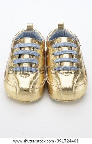 Closeup of golden baby shoes on white background - stock photo