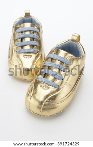 Closeup of golden baby shoes over white background - stock photo