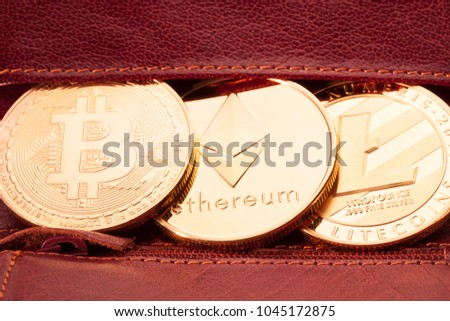 Closeup of golden bitcoin, ethereum and litecoin on the red leather wallet background.
