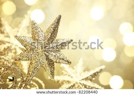 Closeup of golden star on abstract golden light background. - stock photo