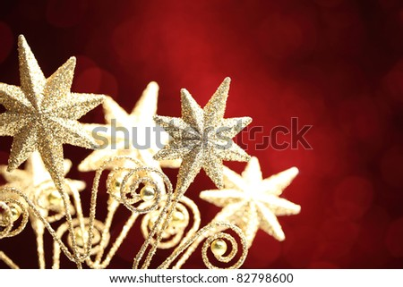 Closeup of golden star on red background.Shallow Dof. - stock photo