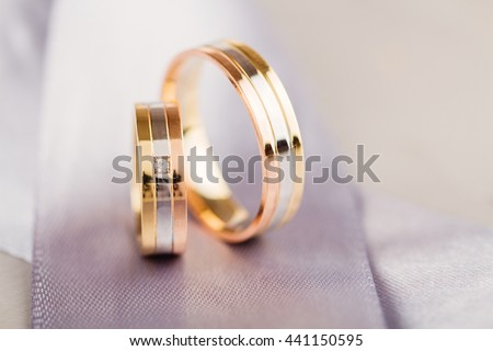 Closeup of golden wedding rings on gray background. Shallow focus
