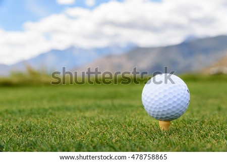 Closeup of golf ball on a tee, on golf course with mountains in the background