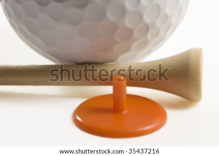 Closeup of golf ball with tee and marker - stock photo