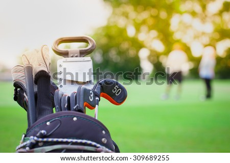 closeup of golf club in bag on golfer background - stock photo
