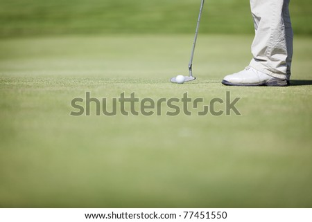 Closeup of golf player putting ball on green, with plenty of copy space. - stock photo