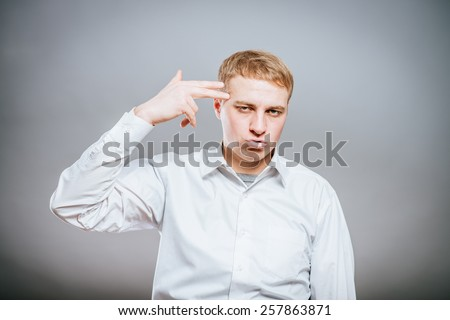 Closeup of good looking young man committing suicide with imaginary gun over  - stock photo