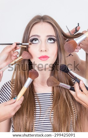 closeup of gorgeous blond girl getting hair and makeup done isolated over white - stock photo