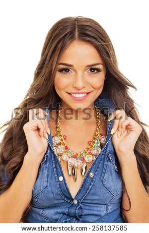 Closeup of gorgeous modern young brunette woman smiling. Beautiful girl in blue denim shirt and modern golden necklace posing happy isolated on white background. Retouched, no color filter. - stock photo