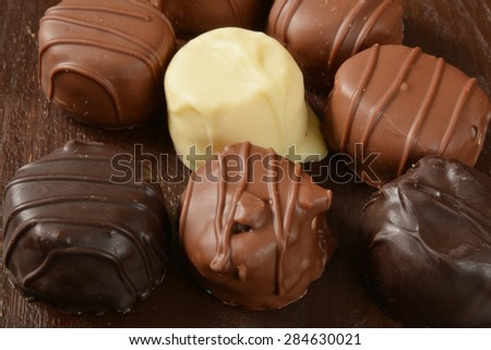 Closeup of gourmet assorted chocolates on a dark wooden table - stock photo