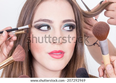 closeup of gprgeous blond girl getting hair and makeup done by many hands isolated over white - stock photo