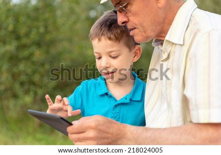 Closeup of grandchild teaching to his grandfather to use a electronic tablet over nature background. Generation values concept. - stock photo