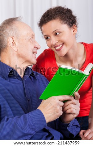 Closeup of grandfather and granddaughter reading book - stock photo