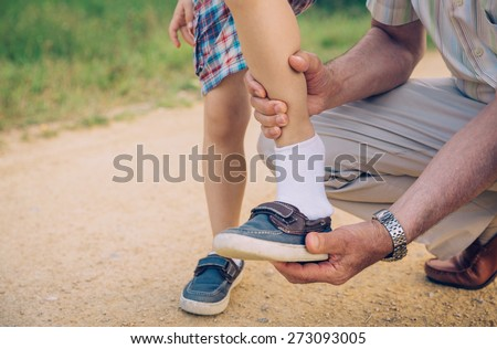 Closeup of grandfather putting shoe to his grandson over a nature pathway background - stock photo