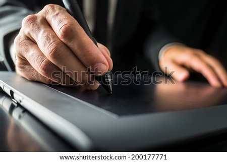 Closeup of graphic designer using digital tablet to do his work. - stock photo