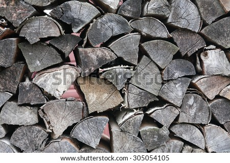 Closeup of gray dry fire-wood. Farm background