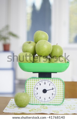 closeup of green apples on kitchen scale - stock photo