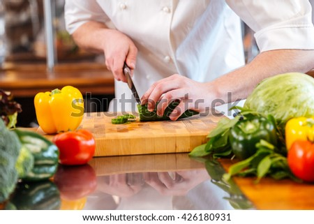 Closeup of green fresh cucumber cut by hands of professional chef cook on the kitchen - stock photo