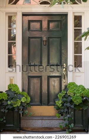 closeup of green front door with lunette and side windows in white door frame with greenery