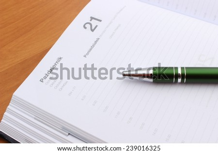 Closeup of green pen lying on open organizer on a desk