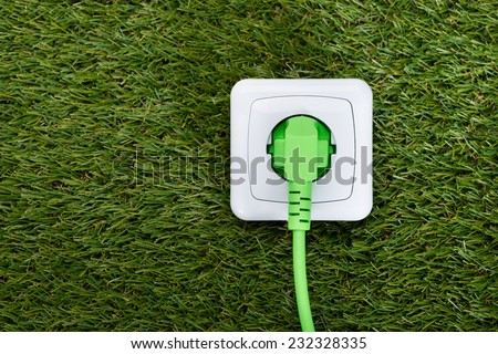 Closeup of green plug in outlet on grass - stock photo