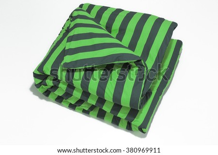 Closeup of green striped comforter on white background - stock photo