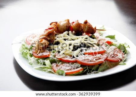 Closeup of grilled beef and vegetable kebabs with salad and potatoes.  - stock photo