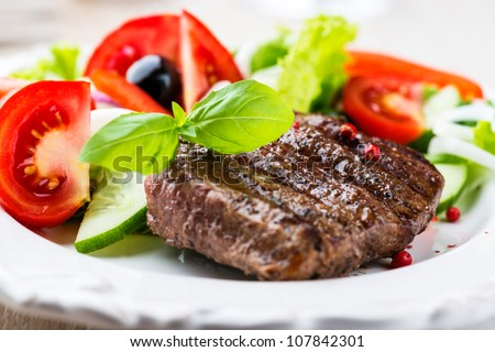 Closeup of grilled beef steak with fresh vegetables - stock photo