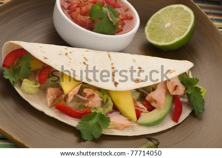 Closeup of grilled salmon fish tacos served with guacamole, fresh tomatoes salsa, and tortilla chips.
