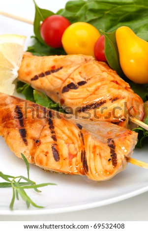 Closeup of grilled salmon on bamboo sticks and vegetable skewers with fresh tarragon and green salad - stock photo