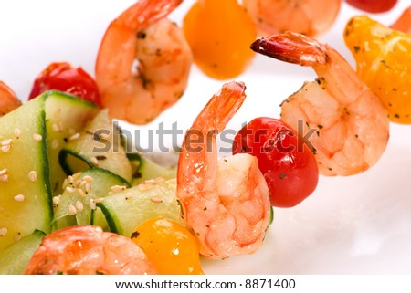 Closeup of grilled shrimps and pear tomatoes on bamboo sticks served with cucumber sesame salad in dinner setting. Shallow DOF, focus on first row. - stock photo