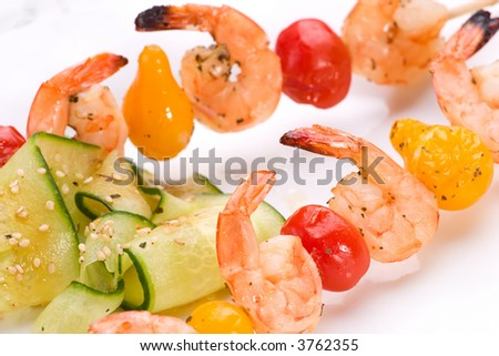 Closeup of grilled shrimps and pear tomatoes on bamboo sticks served with cucumber sesame sald in dinner setting. Shallow DOF, focus on first row.