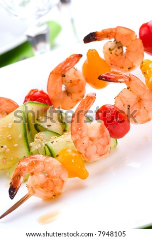 Closeup of grilled shrimps and pear tomatoes on bamboo sticks served with cucumber sesame sald in dinner setting. Shallow DOF, focus on first row. - stock photo