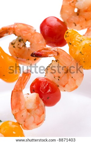 Closeup of grilled shrimps and pear tomatoes on bamboo sticks. Shallow DOF, focus on first row. - stock photo