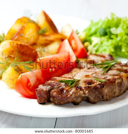 Closeup of grilled steak with baked potatoes and herbs