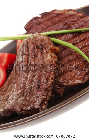 closeup of grilled steak with pasta and tomatoes on dark plate isolated over white background