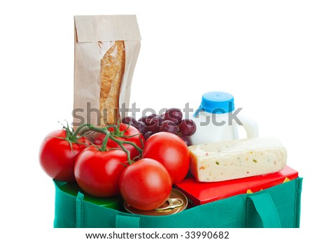 Closeup of groceries in a eco-friendly, reusable, green cloth bag.  Shot on white background. - stock photo