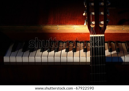 Closeup of guitar standing near open piano on dark background with lighting effect - stock photo