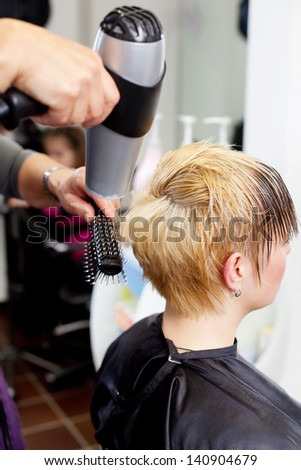 Closeup of hairdresser drying client's hair in salon - stock photo