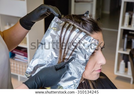 Closeup of hairdresser hands separating strands of hair of beautiful young woman with aluminium foil before change the hair color - stock photo
