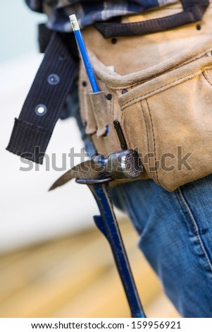Closeup of hammer hanging in tool belt of carpenter - stock photo