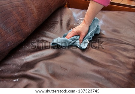 closeup of hand cleaning and conditioning a leather couch with conditioning product and blue microfiber cloth - stock photo