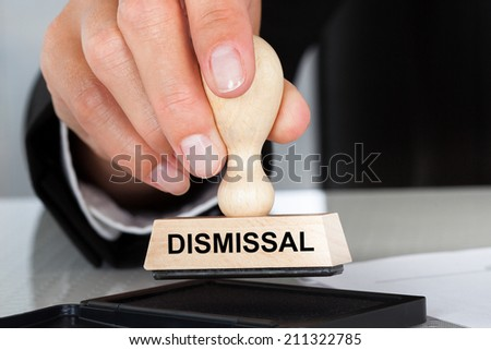 Closeup of hand holding rubber stamp with Dismissal sign at table in office