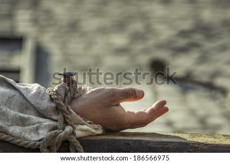 Closeup of hand nailed on wooden cross. Crucifixion of Jesus Christ. - stock photo